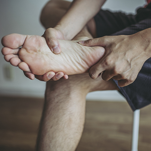 person suffering from foot pain